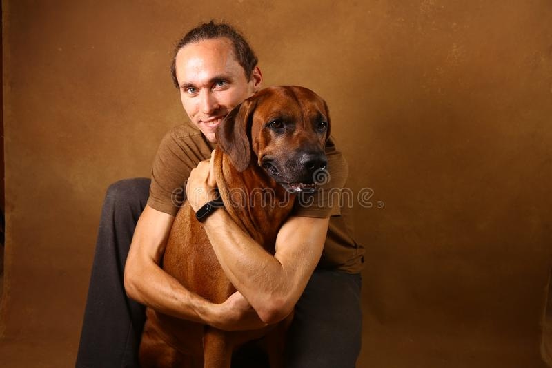 Studio shot of a man with Rhodesian Ridgeback Dog on brown Background. Front view at a a man hugging Rhodesian Ridgeback Dog sitting on brown background in stock photography