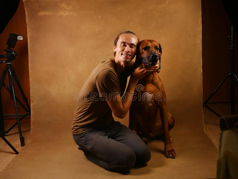 Studio shot of a man with Rhodesian Ridgeback Dog on brown Background. Front view at a a man hugging Rhodesian Ridgeback Dog sitting on brown background in royalty free stock image