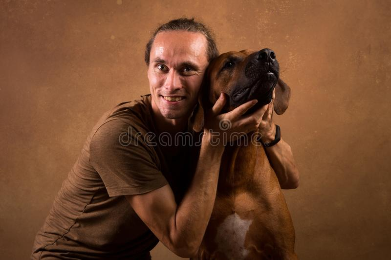 Studio shot of a man with Rhodesian Ridgeback Dog on brown Background. Front view at a a man hugging Rhodesian Ridgeback Dog sitting on brown background in royalty free stock images