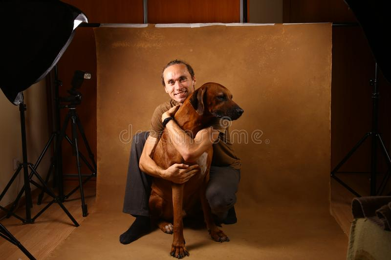 Studio shot of a man with Rhodesian Ridgeback Dog on brown Background. Front view at a a man hugging Rhodesian Ridgeback Dog sitting on brown background in stock photo