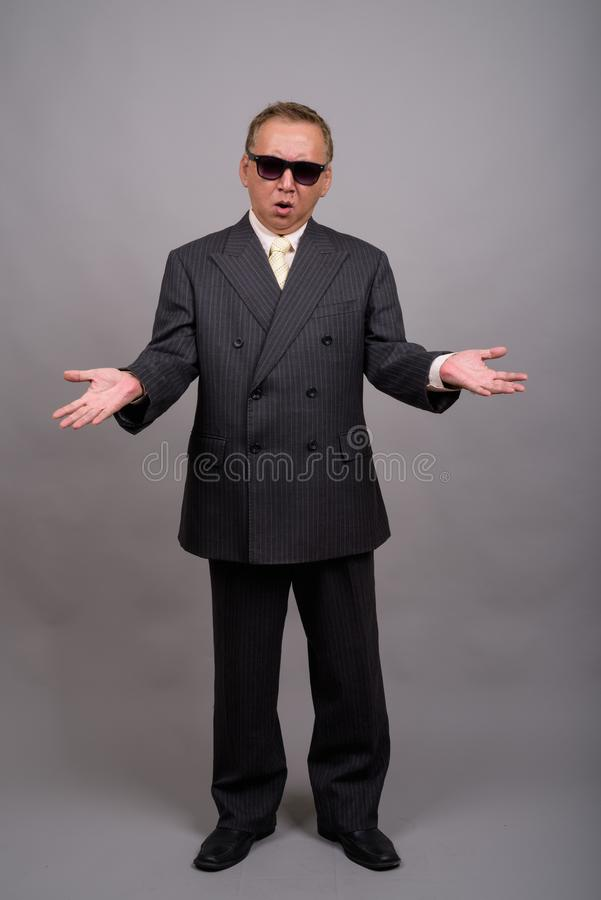 Portrait of mature Asian businessman against gray background. Studio shot of mature Asian businessman wearing sunglasses against gray background royalty free stock image