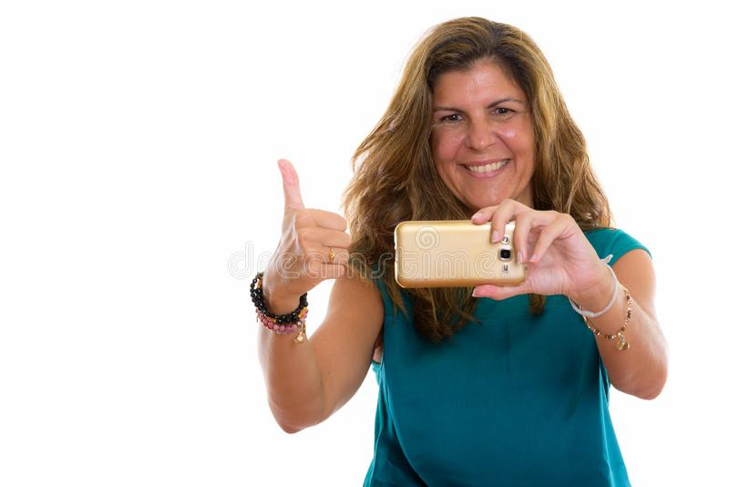 Studio shot of mature happy woman smiling while taking picture w. Studio shot of mature beautiful woman against white background royalty free stock photo