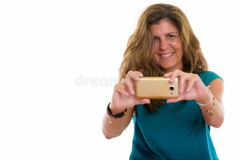 Studio shot of mature happy woman smiling while taking picture w. Studio shot of mature beautiful woman against white background royalty free stock photography