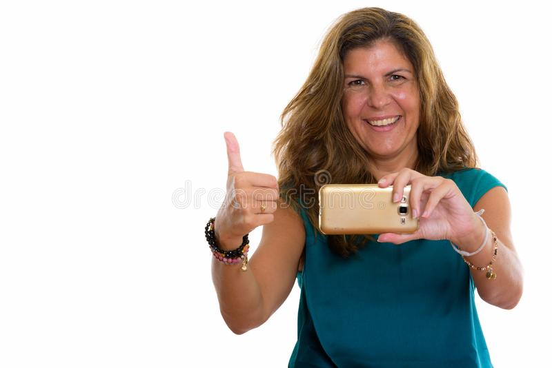 Studio shot of mature happy woman smiling while taking picture w. Studio shot of mature beautiful woman against white background stock photos