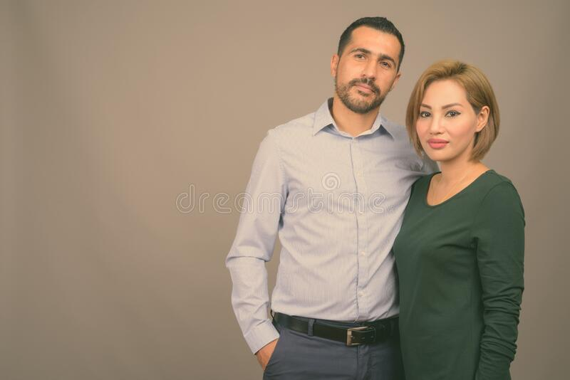 Multi ethnic couple together and in love against gray background stock photography