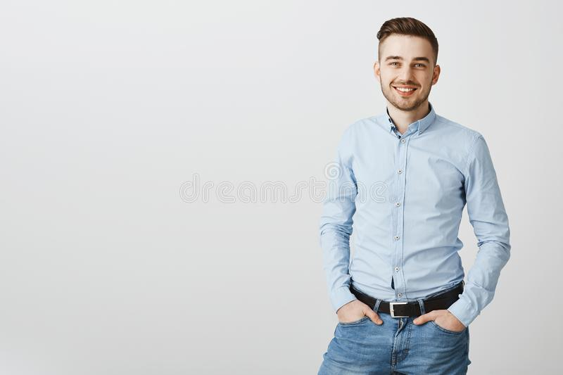 Studio shot of neat stylish handsome young male entrepreneur in blue collar shirt and jeans holding hands in pockets and. Smiling with optimistic friendly smile royalty free stock photos
