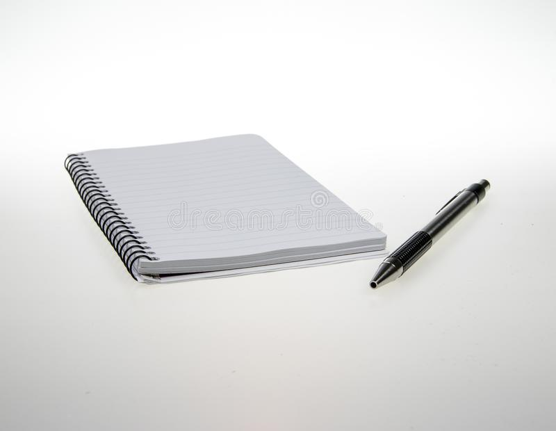 Notepad and pen isolated on a white background. Studio shot of a notepad and ball point pen office supplies isolated on a white background royalty free stock images