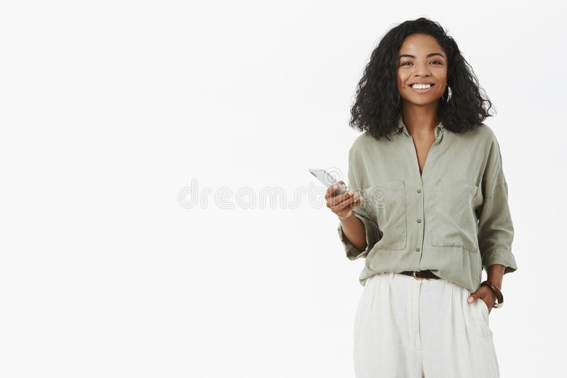 Studio shot of outgoing charistmatic charming african american woman with curly hairstyle holding hand in pocket using. Smartphone gazing with broad smile at stock image