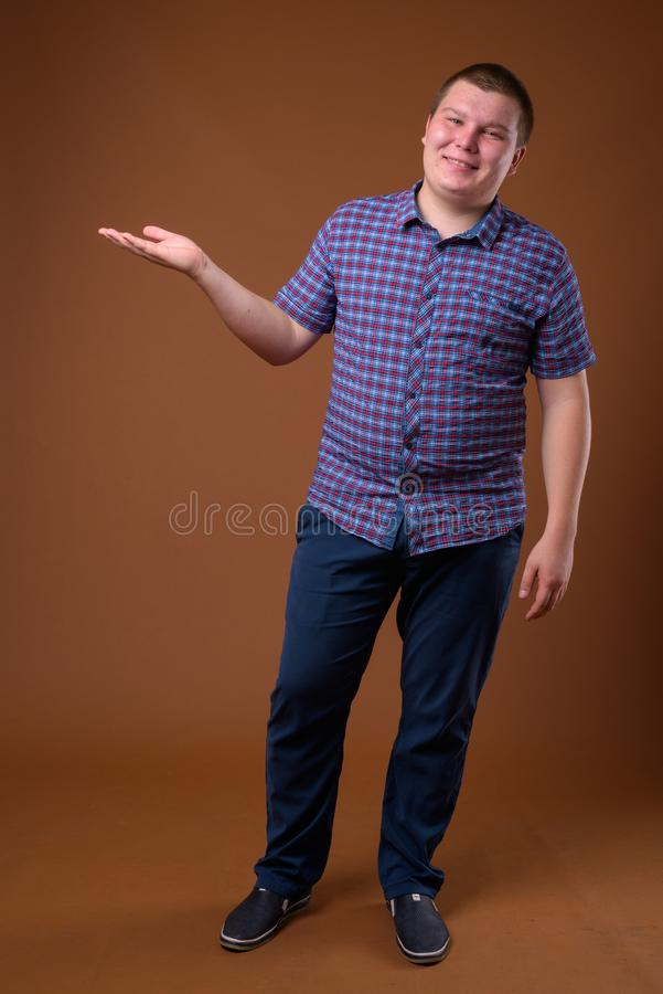 Studio shot of overweight young man against brown background stock photo