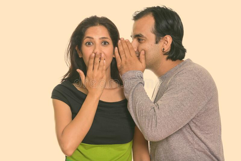 Studio shot of Persian couple with man whispering to woman looking shocked royalty free stock photography