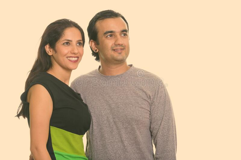 Studio shot of happy Persian couple smiling and looking at distance together stock images