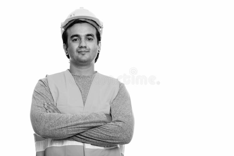 Studio shot of Persian man construction worker with arms crossed royalty free stock photo