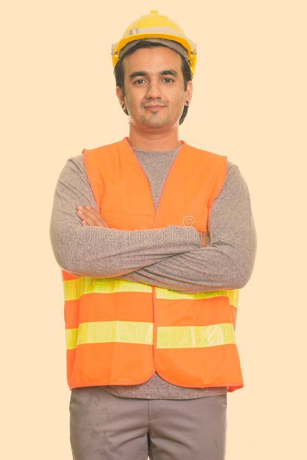 Studio shot of Persian man construction worker with arms crossed royalty free stock photos