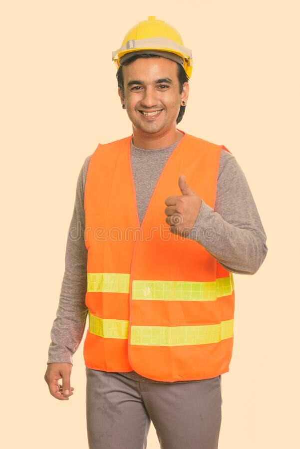 Happy Persian man construction worker smiling while giving thumb up royalty free stock photo