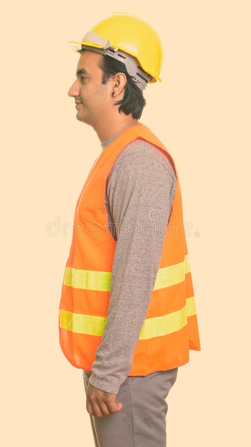 Profile view of happy Persian man construction worker smiling stock photo