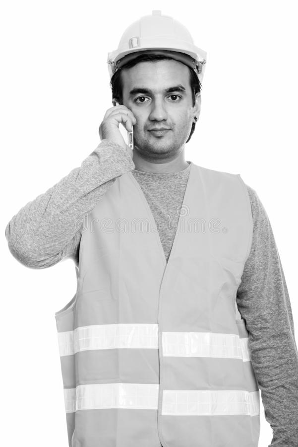 Studio shot of Persian man construction worker talking on mobile phone stock images