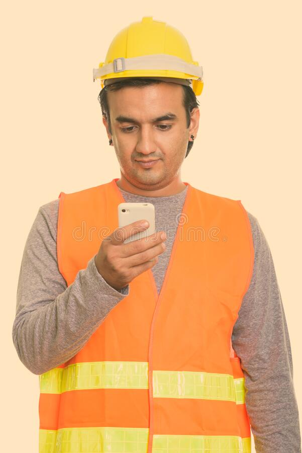 Studio shot of Persian man construction worker using mobile phone royalty free stock photo