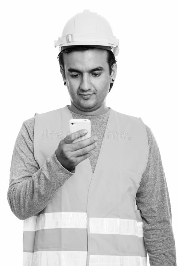 Studio shot of Persian man construction worker using mobile phone stock photo