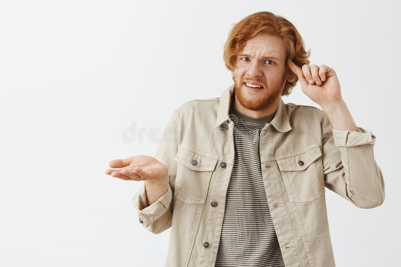 Studio shot of confused and displeased caucasian redhead guy with beard rolling index finger on temple and. Shrugging with disappointed and shocked expression stock photos