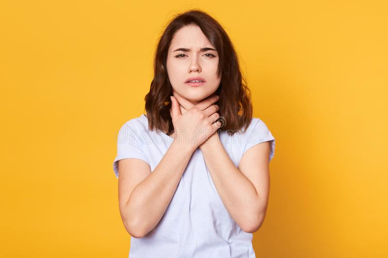 Studio shot of pleasant looking female with upset look, wears white casual t shirt, keeps both hands on neck, poses against yellow royalty free stock image