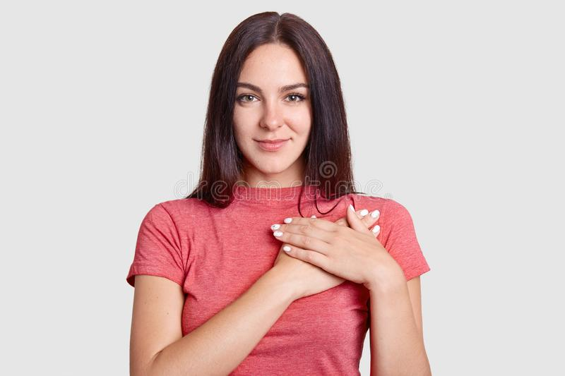 Studio shot of pleasant looking kind hearted young woman keeps hands on chest, expresses gratitude, dressed in casual t shirt, pos royalty free stock photography