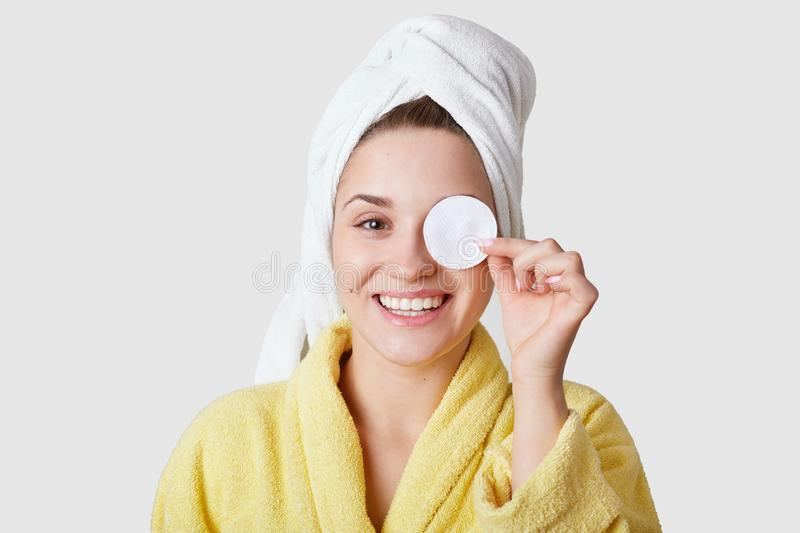 Studio shot of pleasant looking young smiling European woman covers eye with cotton disk, has white towel on head, takes care of stock photos