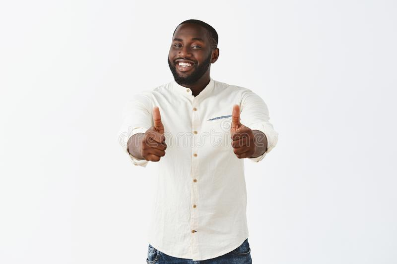 Studio shot of pleased good-looking crafty male african american chef in white shirt, smiling broadly from satisfaction stock photography
