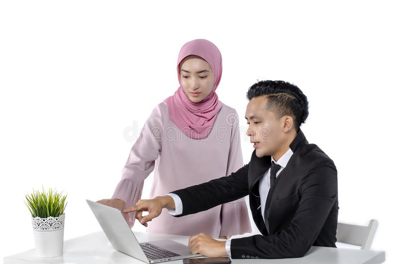 Portrait of young couple entrepreneurs discussing ideas with a laptop in front of them royalty free stock images