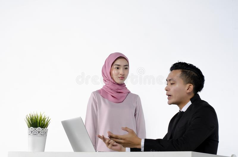 Portrait of young couple entrepreneurs discussing ideas with a laptop in front of them royalty free stock photos
