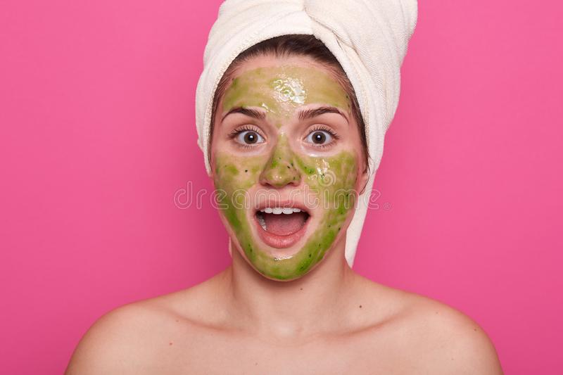 Studio shot of pretty girl with green clay facial mask. Photo of surprised girl with white towel on her head, having astonished stock photos