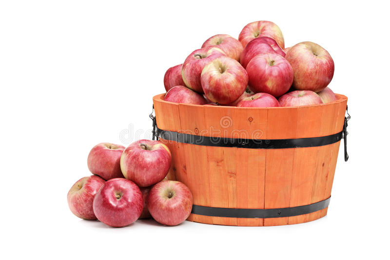 Studio shot of red apples in a wooden bucket. Isolated on white background stock image