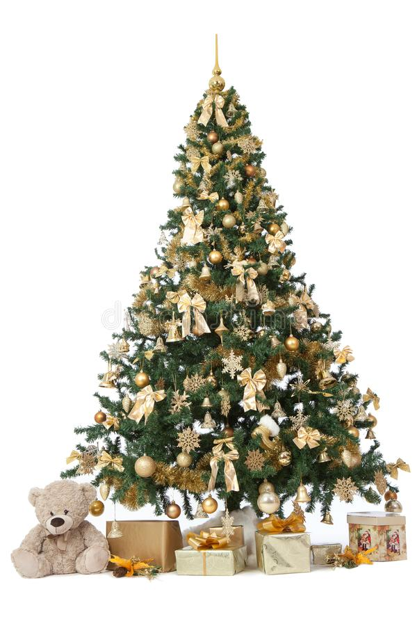 Studio shot of a richly decorated christmas tree with golden ornaments isolated on a white background with a presents stock image