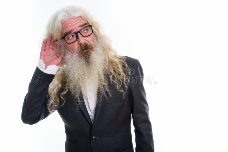 Studio shot of senior bearded businessman thinking while listeni. Ng stock image
