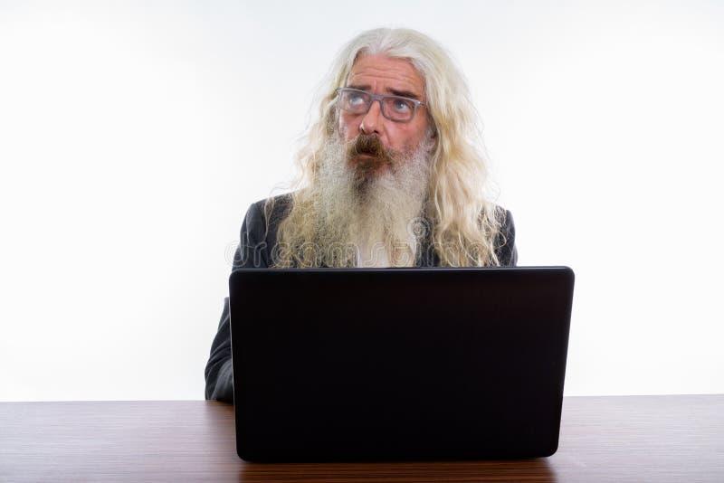 Studio shot of senior bearded businessman thinking and looking u stock photo