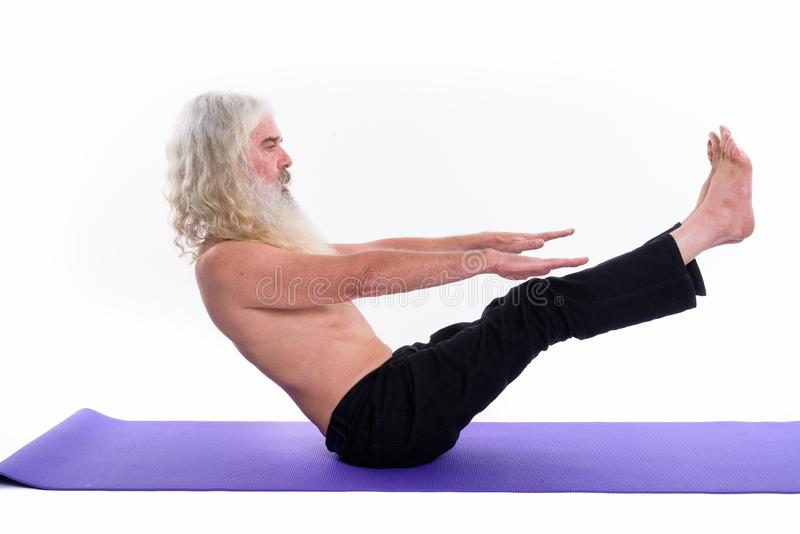 Studio shot of senior bearded guru man doing yoga poses and stretching royalty free stock images