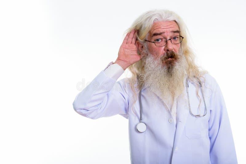 Studio shot of senior bearded man doctor listening. Isolated against white background stock photo