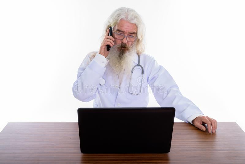 Studio shot of senior bearded man doctor talking on mobile phone. While looking at laptop on wooden table stock photos