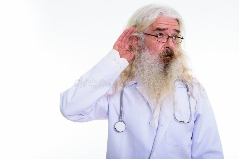 Studio shot of senior bearded man doctor thinking while listenin. G stock images
