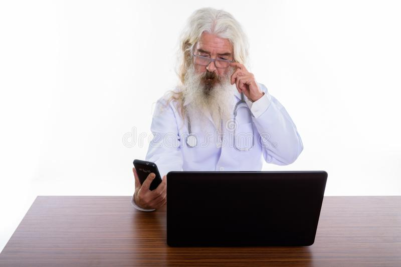 Studio shot of senior bearded man doctor using mobile phone with. Laptop on wooden table royalty free stock images