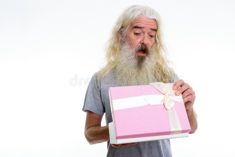 Studio shot of senior bearded man opening gift box while looking. Shocked ready for Valentine`s day royalty free stock photos