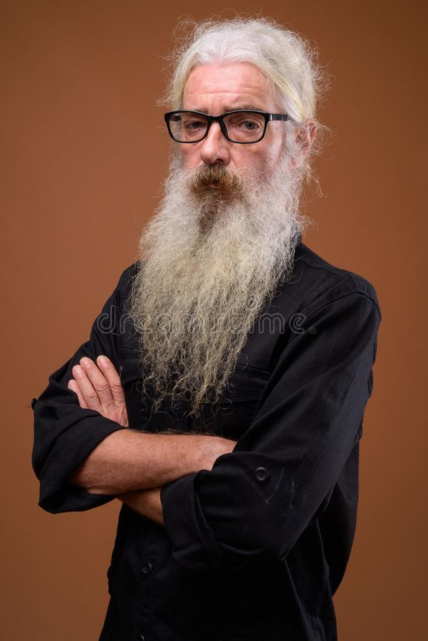 Portrait of senior bearded man against brown background stock images