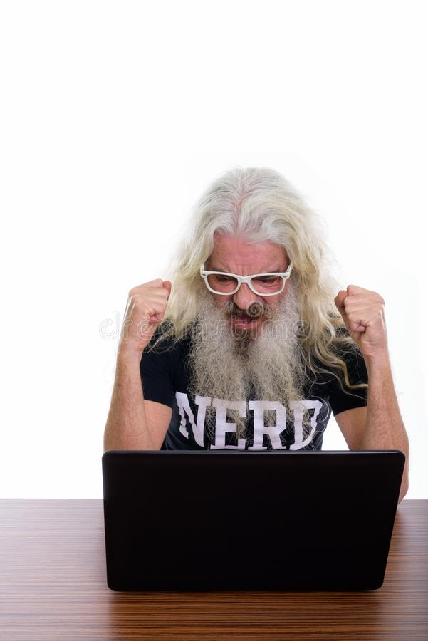 Studio shot of senior bearded nerd man looking motivated while u. Sing laptop on wooden table stock image