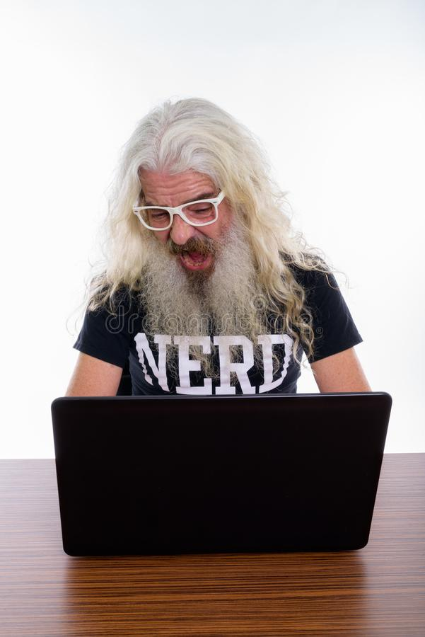 Studio shot of senior bearded nerd man looking shocked while usi. Ng laptop on wooden table royalty free stock photo