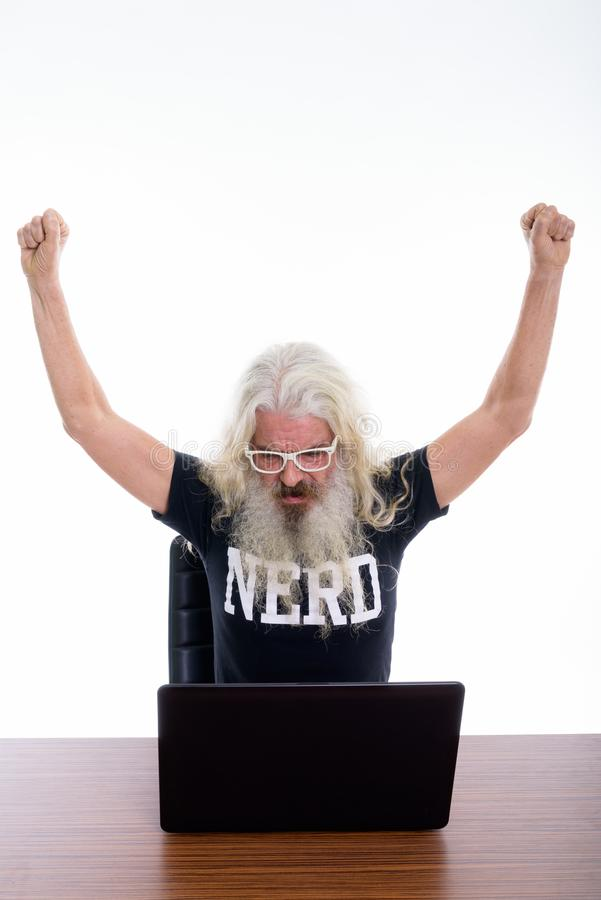 Studio shot of senior bearded nerd man raising both arms and loo. King excited while using laptop on wooden table royalty free stock image