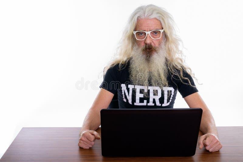 Studio shot of senior bearded nerd man using laptop on wooden ta royalty free stock photo