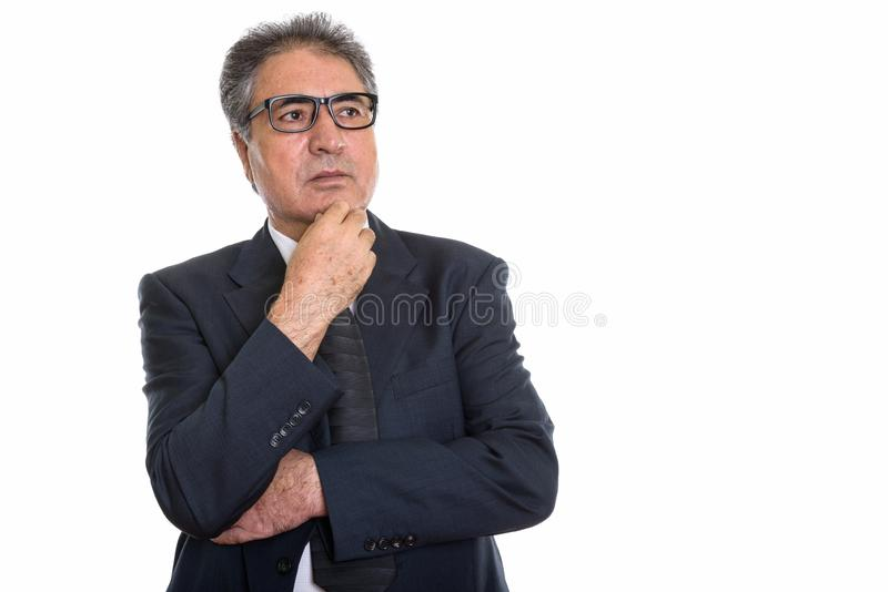 Studio shot of senior Persian businessman thinking and looking a stock images