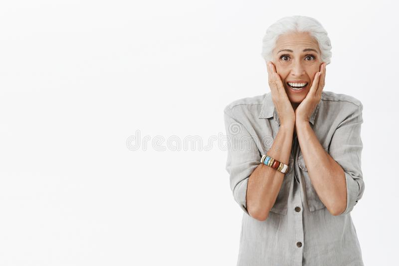 Studio shot of senior woman reacting on surprise. Portrait of touched and delighted cute old lady with white hair royalty free stock photography