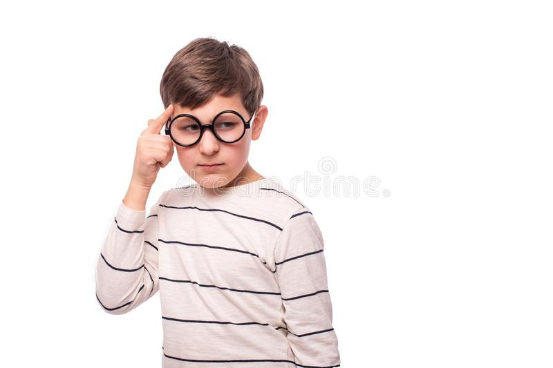 Studio shot of a serious boy  in round glasses, isolate with copy space. He thinks about something important putting his index. Finger to his temple royalty free stock image
