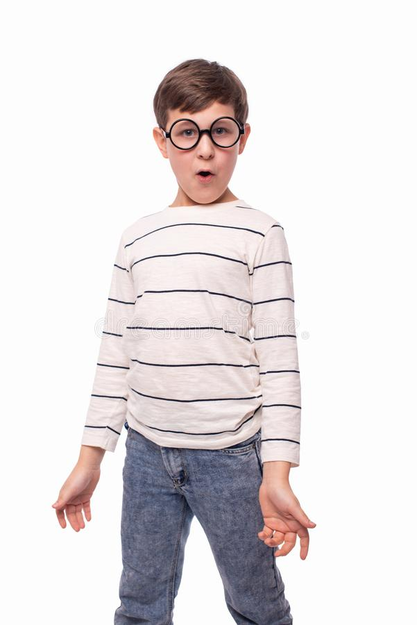 Studio shot of a serious boy in round glasses wondering something spreading his arms to the side, isolated on white with copy stock images