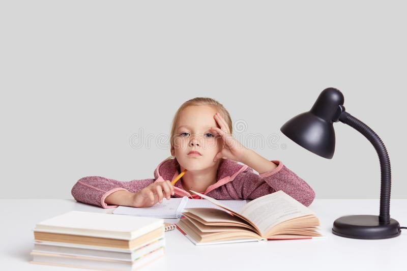 Studio shot of serious intelligent small schoolgirl keeps hand on head, looks with tired expression directly at camera, learns new stock image
